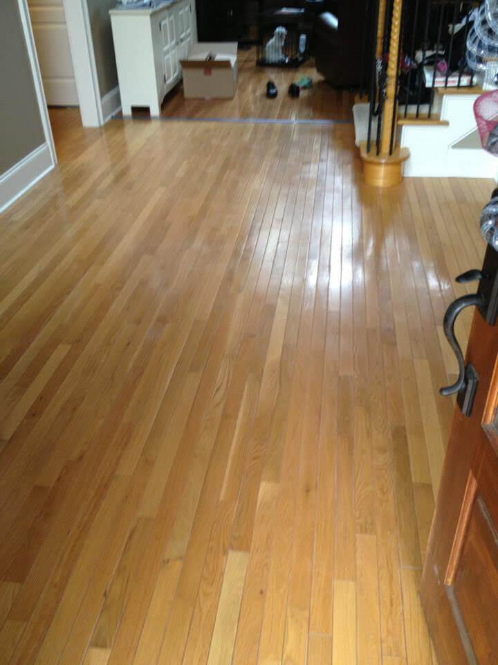 hardwood floor at the base of some wooden stairs.